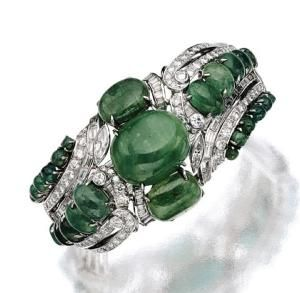 CABOCHON EMERALD AND DIAMOND BANGLE-BRACELET, CIRCA 1940.  The hinged bangle decorated on the front with 25 oval and round cabochon emeralds within an openwork scroll design, further decorated with 2 marquise-shaped, 42 baguette and 106 round and single-cut diamonds weighing approximately 7.50 carats, mounted in white gold. by june