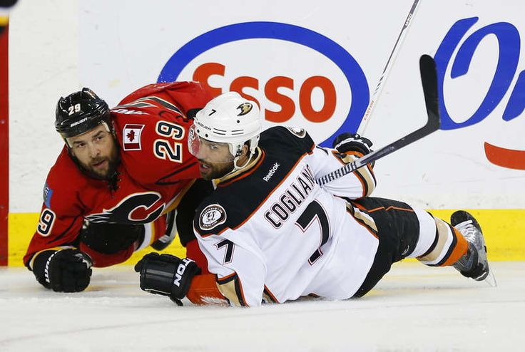 Deryk Engelland #29 of the Calgary Flames and Andrew Cogliano #7 of the Anaheim Ducks hit the ice in Game Four of the Western Conference Semifinals during the 2015 Stanley Cup Playoffs at the Scotiabank Saddledome on May 8, 2015 in Calgary