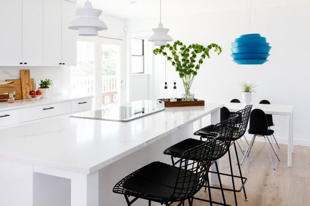 Simple way to dress up a white kitchen is to add pops of color in unexpected ways. Allison Crawford used a blue lantern and black bar stools for contrast. Designer Spotlight | Allison Crawford - The Interior Collective