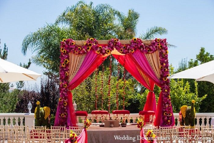 A vibrant floral mandap for an outdoor wedding.