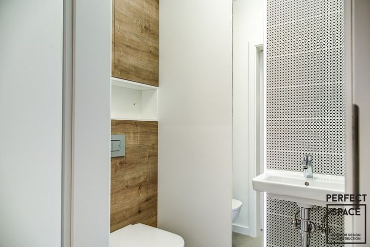 Drewno w łazience, w postaci obudowy nad toaletą oraz szafki.