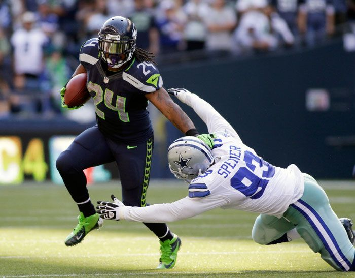 seahawks football | Seattle Seahawks running back Marshawn Lynch (L) carries the football ...