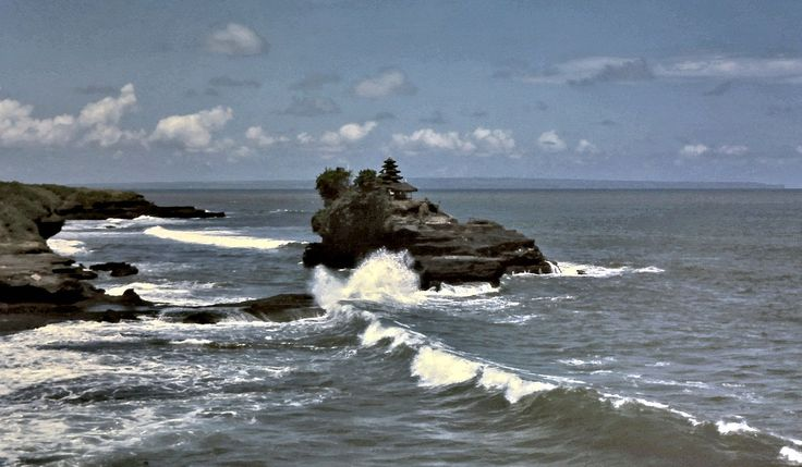Tanah Lot temple and heavy surf looking southeast on the south coast of Bali, Indonesia in 1975. The far background in this view ranges from Kuta beach to Ulu Watu point.