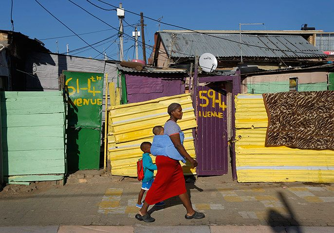 A mother walks her child to school past brightly coloured shacks in Alexandra Township