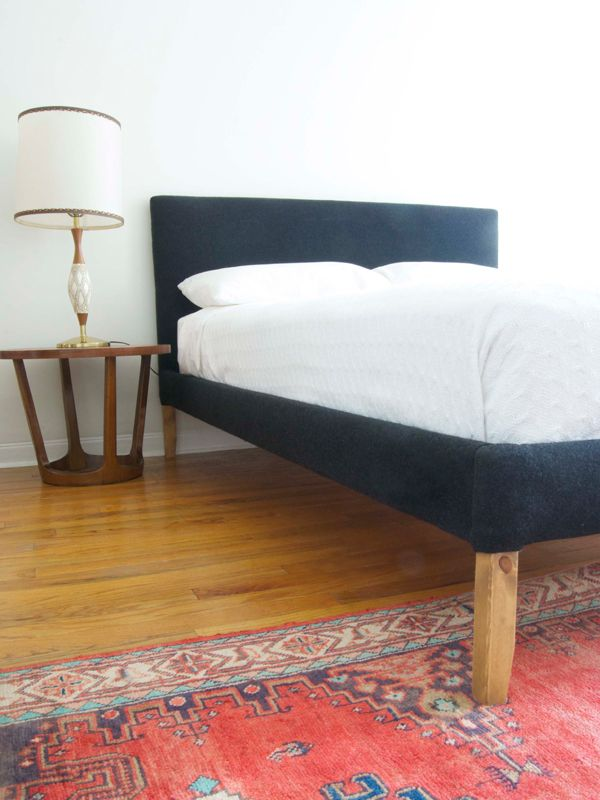 A boring pine bed bed frame gets a brand-new look with the help of some felt, wool fabric, and 1,250 staples (no big deal).