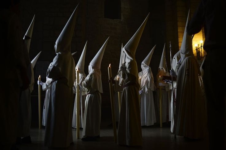 Penitents of the 'La Borriquita' brotherhood take part during a Holy Week procession in Cordoba, southern Spain. Hundreds of processions take place throughout the country during the Easter Holy Week