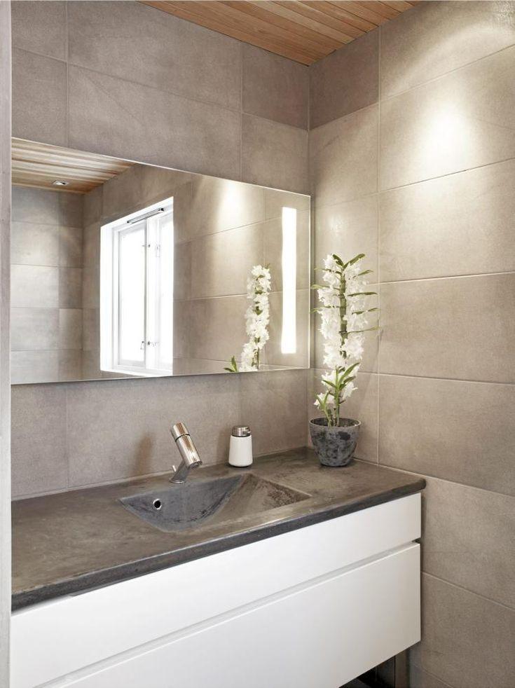 Harmaa iso laatta sekä betonitaso valkoisilla kalusteilla. Tätä tyyliä haen!