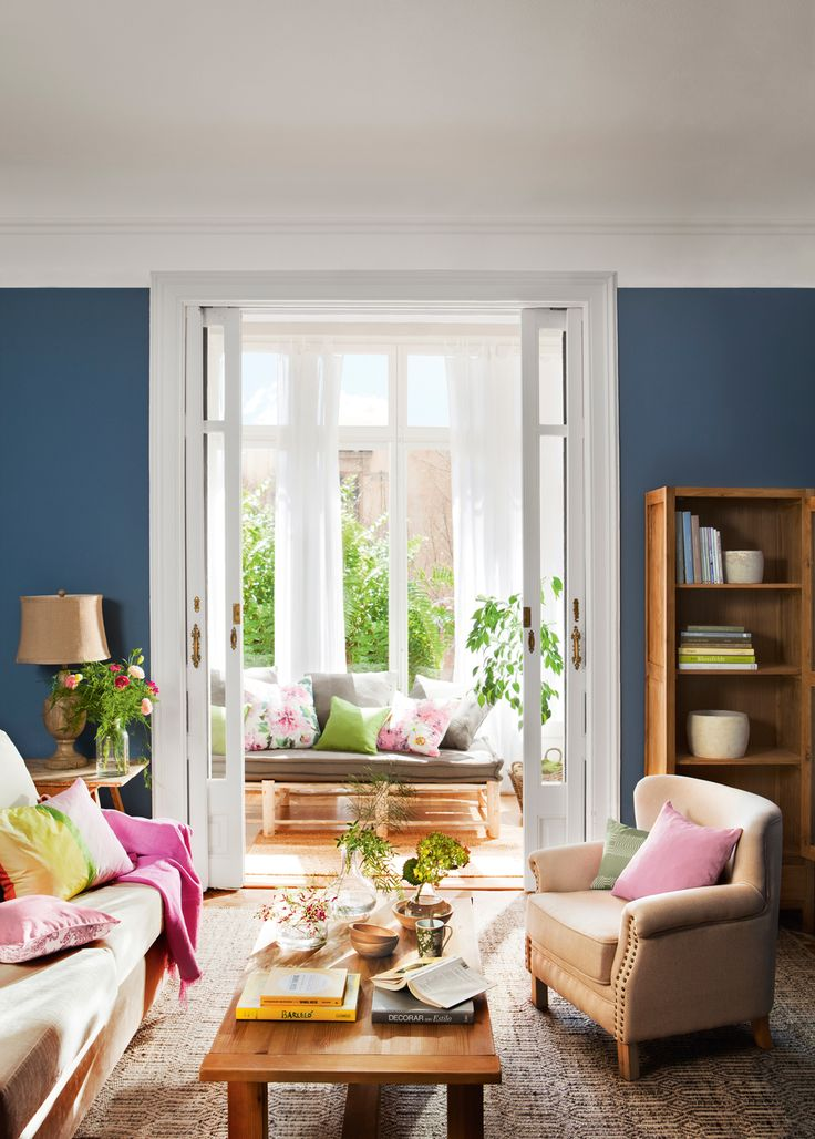 Salón clásico de puertas correderas blancas, paredes en azul intenso, sofás claros y cojines rosados y lámpara de lágrimas 00404173