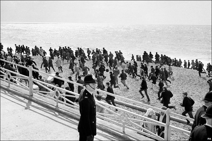 Mods run along the beach at Brighton in April 1964