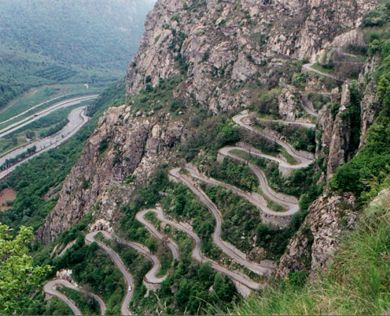 "Col du Chaussy in southeastern France is a high mountain pass 5,030 feet above the sea level. ""The road to reach the summit starts with the famous 'Hairpins de Montvernier,' a special 3 km stretch with 17 hairpins as the road virtually climbs a cliff.""  (3km = 1.86 miles)"
