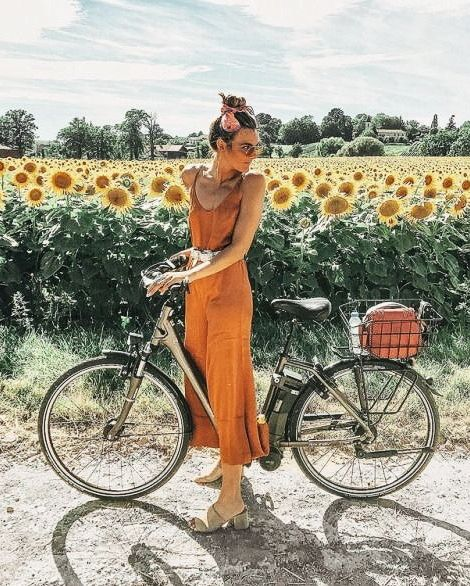 Golden mustard dress jewel tone on a bicycle in front of a sunflower field
