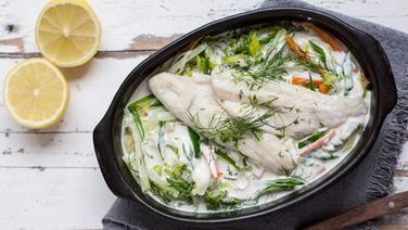 Rezepte bei ADIPOSITAS Fischpfanne mit Frühlingsgemüse in einem Bräter auf dem Tisch.