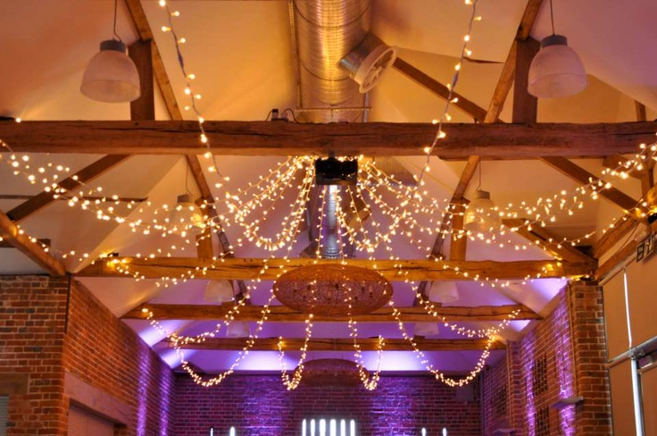 Star canopy of fairy lights in the Castle Barn, Wasing Park. Wedding lighting by Oakwood Events Ltd.