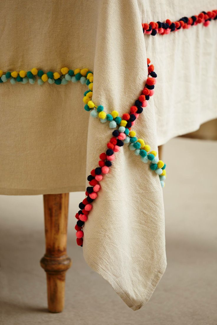 Nomades Table Linen - anthropologie.com (I love this idea to spruce up and fun-up the plain cream linen curtains I have packed away somewhere! Yay PomPom trim!)