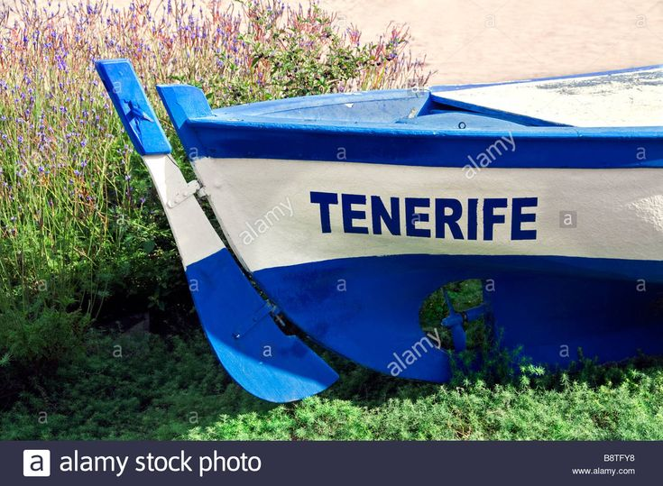 Download this stock image: Feature traditional wooden fishing boat named 'Tenerife' lying on Los Cristianos beach Tenerife Canary Islands Spain - B8TFY8 from Alamy's library of millions of high resolution stock photos, illustrations and vectors.