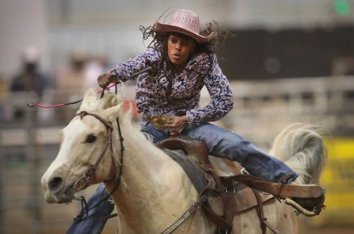 A Cowgirl participates in the barrel race competition with the Bill Pickett Invitational Rodeo.