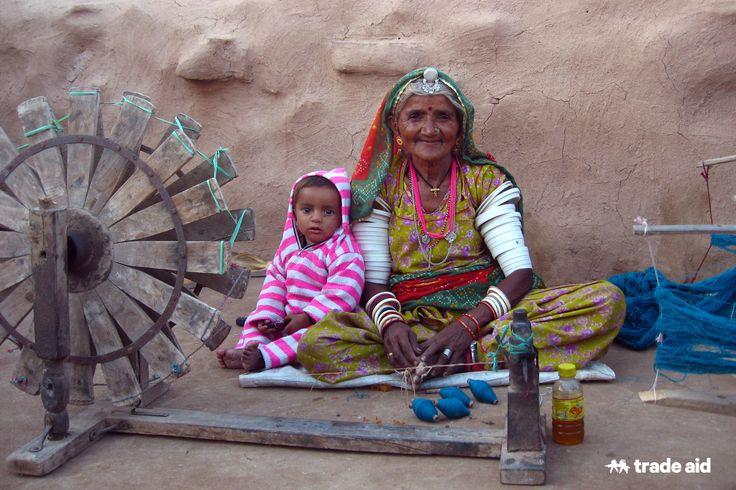 Grandmother sitting spinning bobbins amongst young children. Fair trade - handmade change.