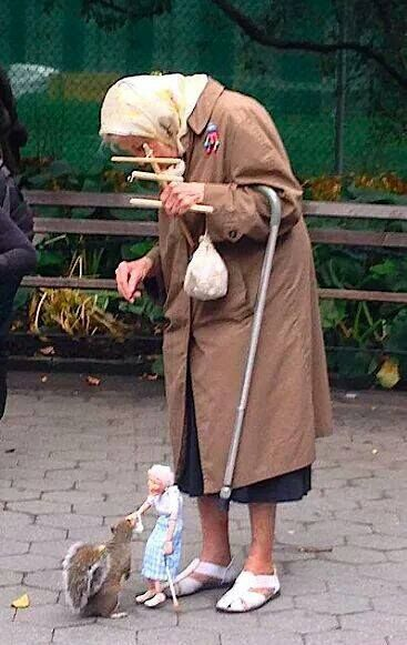 The lady has a puppet feeding the squirrel. Divine!