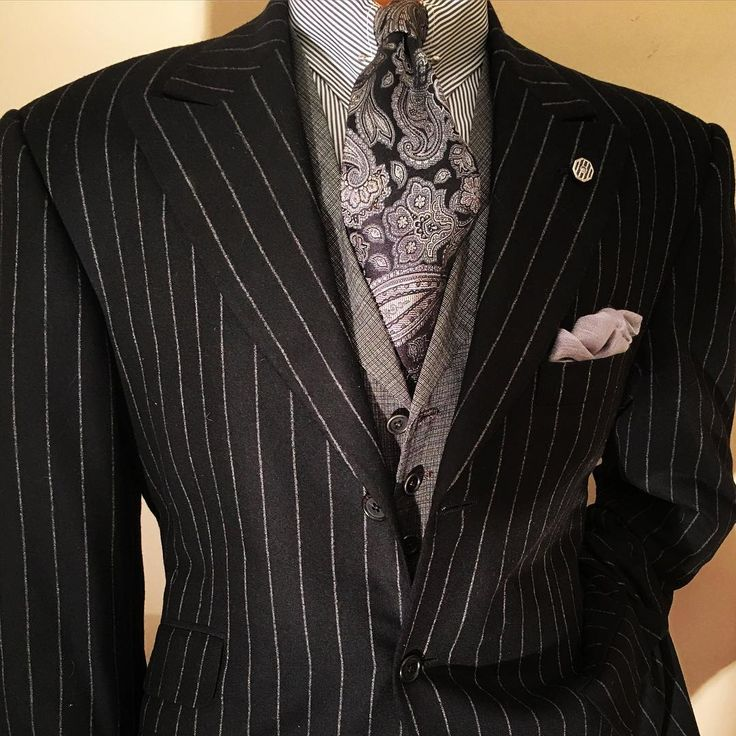 The black Escorial flannel chalk stripe suit. Here, in our three button peak with high twist waistcoat. The tapestry tie is on a satin ground, and the point collar shirt is 140s two ply. Cashmere and silk pochette; 1930s sterling collar bar and lapel pin. The pochette, or pocket square, can be traced to the Ancient Greeks, who carried a cloth with scented perfume in order to ensure that an inviting smell always accompanied them. Later, Roman gladiator games were begun when the Emperor…