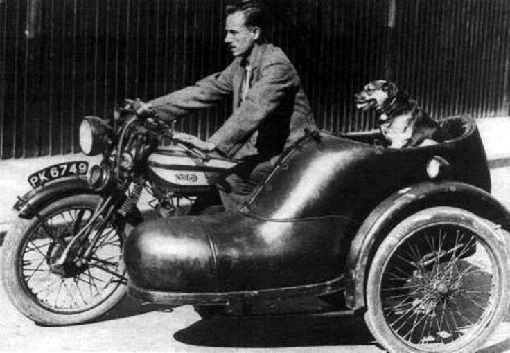 """This photo shows an enterprising shoemaker who had a sidecar for his motorcycle made in the form of a shoe. The Norton is a 16H fitted with Druid forks; note the non-tapered tubes. The dog is of unknown breed and year.  Martin: """"The registration number series 'PK' was issued by the Surrey County Council (south west of London) between May 1928 and May 1929 which indicates a 1929 model."""" via"""