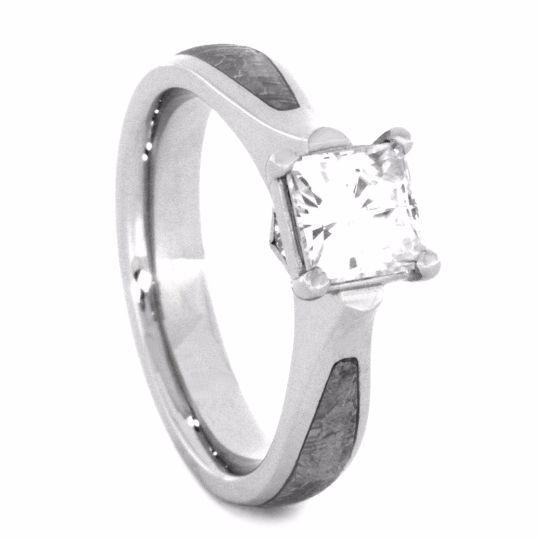 A glorious, princess cut moissanite sits atop this 10k white gold engagement ring. The white gold ring is further enhanced with a gorgeous meteorite...