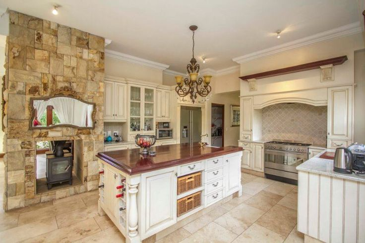 House For Sale in DAINFERN VALLEY, SANDTON:  Entertaining is easy on the wide patio with built-in braai and stacking doors through to the living rooms. Guests may well join you in the country-style kitchen, open-plan as it is, and no less inviting and handsome than the living rooms, with its chandelier, display cabinets, feature stone wall and fireplace.