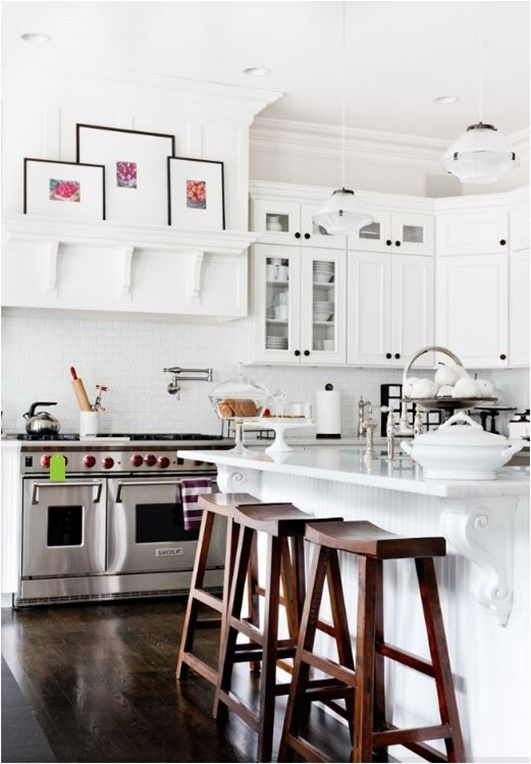 White kitchen. Art above the hood. Dark floors and benches. Love it.
