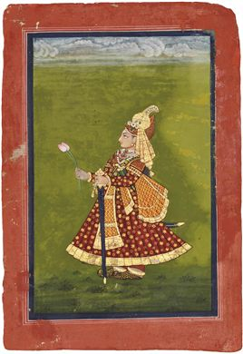 MAHARAJA HAMRAV SINGHJI OF DEVGARH, RAJASTHAN, INDIA, CIRCA 1820. Opaque pigments and gold on paper, standing facing left, richly dressed, wearing an elaborate bejewelled turban, holding two lotus buds and his sword, on green ground with clouds at top, with blue margins and red borders.