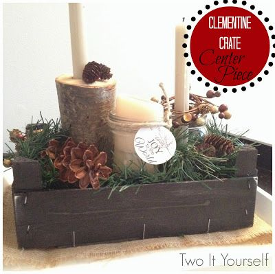 Christmas Table Decorations: Spray paint a wooden clementine crate and fill it with candles, garland and pine cones