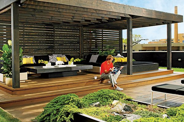 On the 1,500-square-foot deck, an ebony-stained cedar pergola shelters low-slung '60s Italian fiberglass seating pods topped with Sunbrella-upholstered cushions, all surrounding a crisply geometric cedar coffee table with a black marble mosaic top designed by homeowner Daran Puffer.