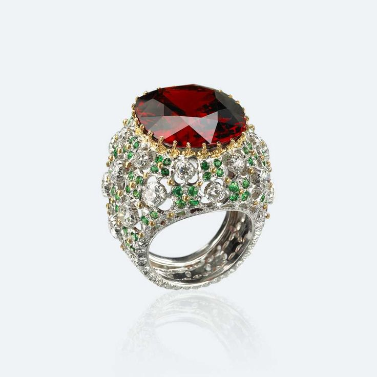 The intense red color of the central stone dominates the openwork white gold surface, enhanced by diamonds and tzavorites, thus creating an extremely harmonious color combination, of great visual impact. Nothing is by chance, everything contributes to form a large garden where the most important flower stands out imposingly in the center. Among all the Cocktail Rings in the collection, this one amazes for the beauty of the stone and the harmony of the design.