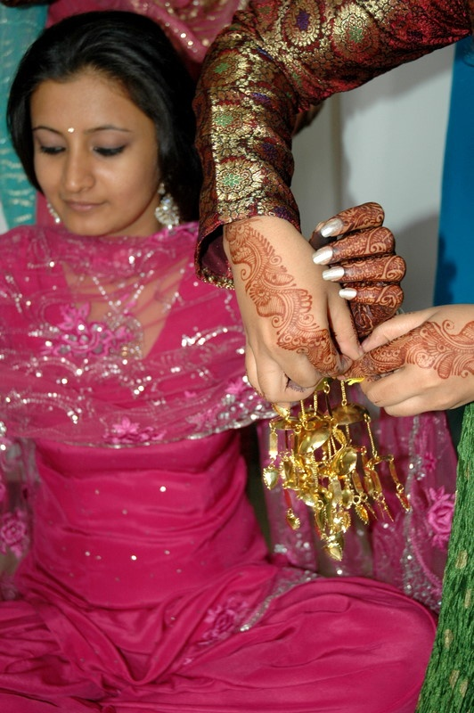 A punjabi bride being dressed up in the traditional way on her wedding day. Punjabi weddings are full of colour and grace.