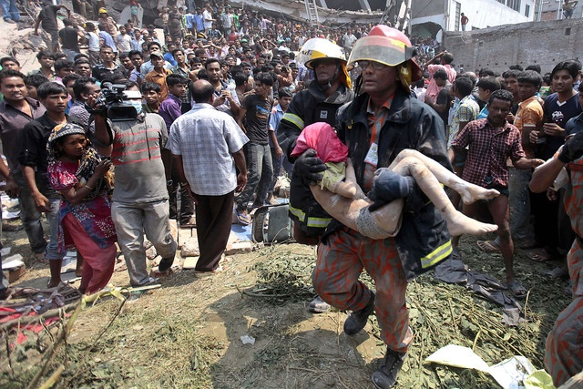 Horror in Bangladesh| Rescue workers carry a young victim's body after an eight-story building housing several garment factories collapsed in Savar, near Dhaka, Bangladesh, on April 24, 2013. | Photo: A.M. Ahad/AP Photo