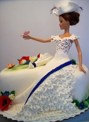 Fashion doll in ruffled gown, posed in garden setting, with fashionable hat, parasol, and flowers