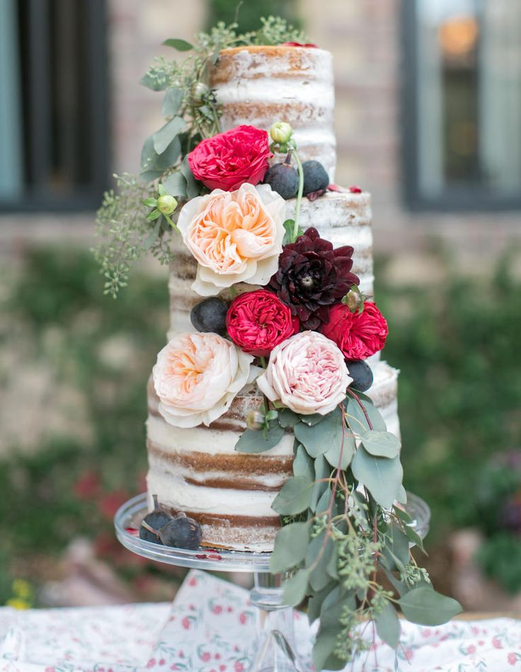 A slim tower of tall tiers outfitted with a romantic cascade of seeded eucalyptus and Juliet garden roses is enough to make anyone think twice about cutting into this beautiful cake.
