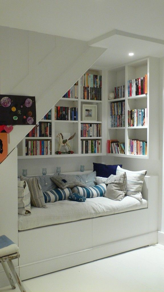 idea for basement under stairs with sofa with built in storage and shelving