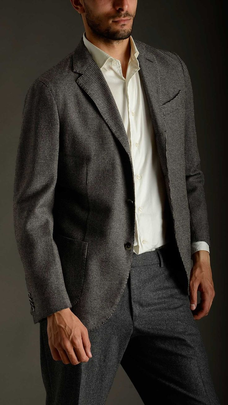 Houdstooth grey and black wool deconstructed blazer featuring three buttons lapel roll, Neapolitan shoulder, long sleeves, four buttons cuffs, peak lapel, regular drop, two patch pockets and a chest pocket at front, inner pockets, 100% wool.