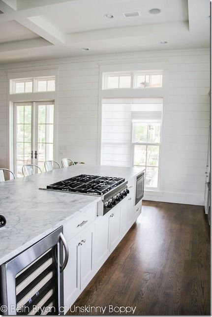 Textured walls. Awesome ceiling. Huuuuge island. White with dark wood floors. Stove/microwave/wine fridge location.