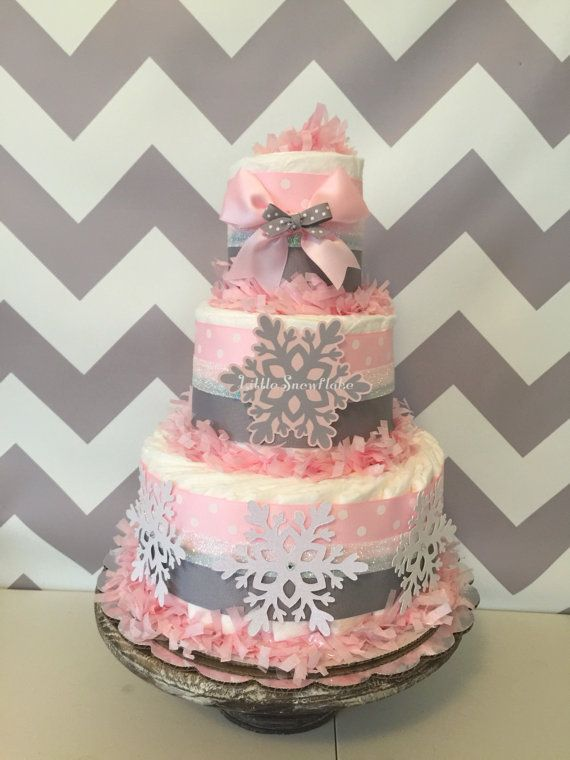 This popular Chevron Winter Wonderland Diaper Cake is our top selling design! Decorated in pink and gray color scheme along with handcrafted snowflakes in coordinating pink and silver. Designed with brand name diapers and high end materials this baby shower set would make the perfect accent to the themed baby shower!  WINTER WONDERLAND DIAPER CAKE INCLUDES: ------------------------------------------------------------------------------------------------ 40-45 Pampers Swaddlers Disposable…