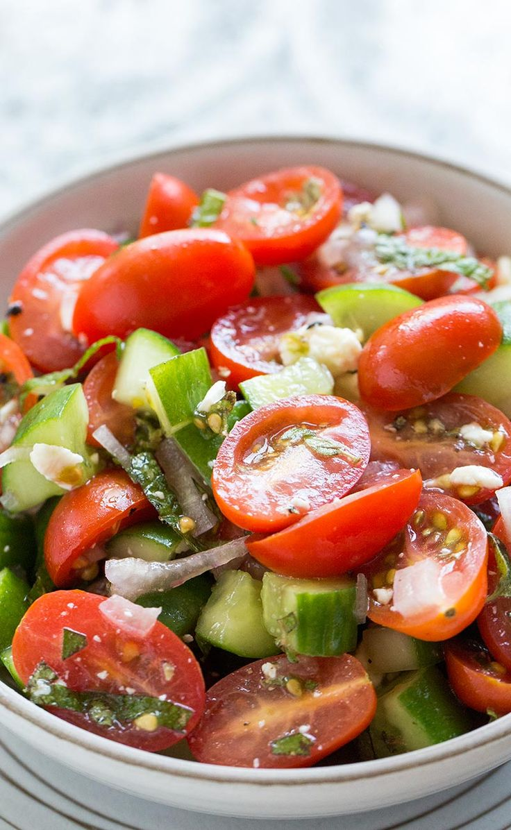 Simple cherry and pear tomato salad with cucumbers, feta cheese, shallots, mint, and oregano. On SimplyRecipes.com
