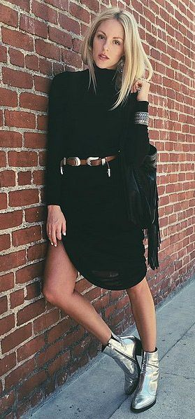 A simple black dress paired with a western belt and metallic boots