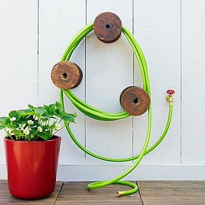 use old wooden spools big ones to make a garden hose holder