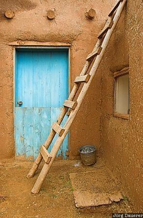 Taos Pueblo blue door against adobe.