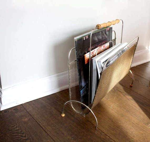 1950s gold tone metal magazine rack with curved/semi-circular feet and with a bamboo handle. Metal mesh body. There are two sections in the