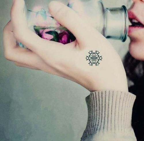 Little hand tattoo of a snowflake.