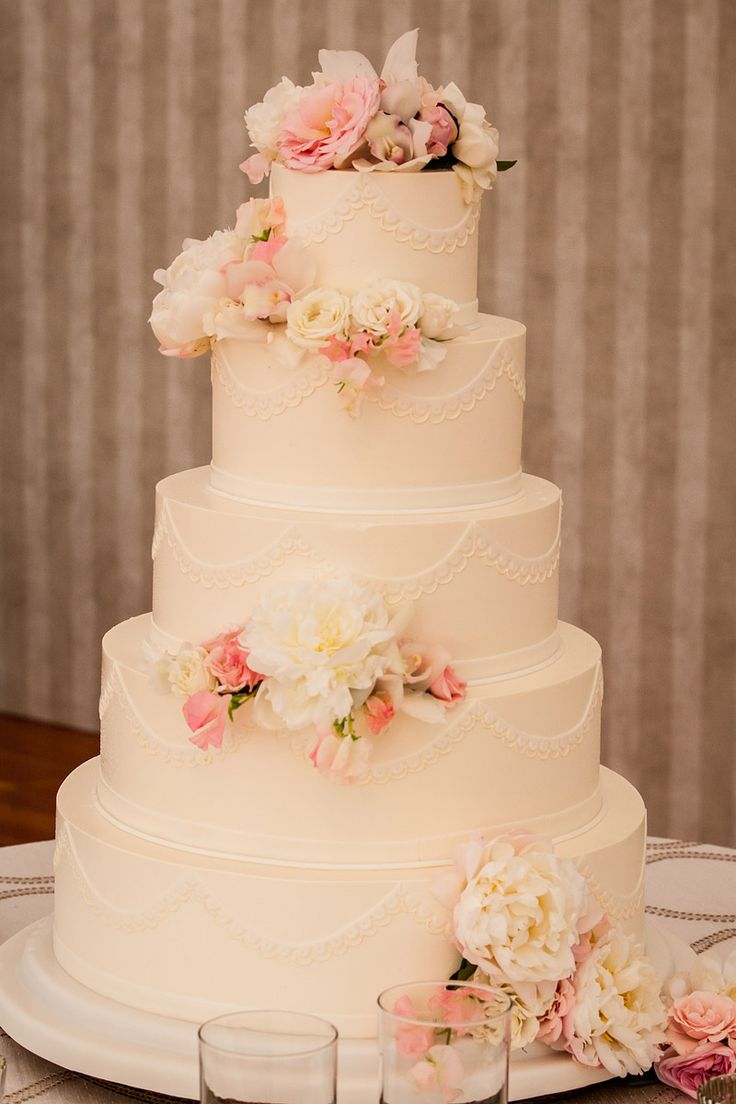 The wedding cake by Mark Soliday at Confectionary Designs in Newport, decorated with peonies and roses. Photographed by Brian Wedge