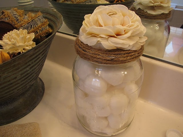 This is a pickle jar with twine around the lid and a flower glued to the top.  Very cute !