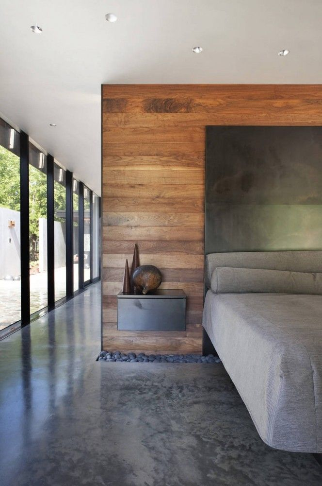 Love this modern bedroom Modern finish with concrete floors, pebble feature, wood accent wall with a metal headboard Heavy Metal / Hufft Projects