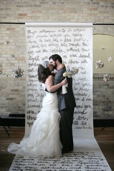 Creative DIY Wedding Ceremony Backdrop ~ Says: This ceremony backdrop has to be the coolest wedding DIY I have seen yet.   The creative couple hand wrote poems on a long roll of butcher paper that was rolled out in place of an aisle runner. During the ceremony, the couples' mothers read the poems.  How touching!