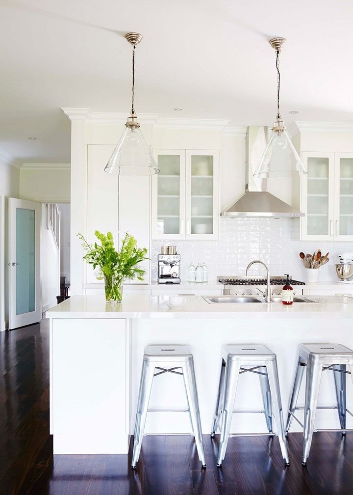 Classic all-white kitchen with stainless steel bar stools adding a contemporary touch | Home Beautiful Magazine Australia